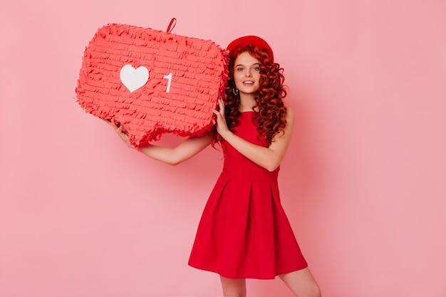 Ognista czerwona kręcona dama w kapeluszu i sukience patrzy na kamerę i trzyma jak znak na odizolowanej przestrzeni.