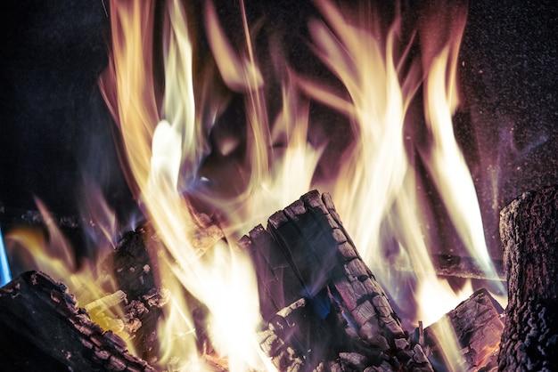 Ogniste, żółte, pomarańczowe języki na ciemnym tle wznoszą się w ceglanym kominku płonącym płomieniem, zimne stonowane