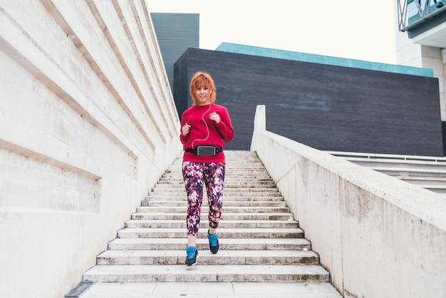 Ogólne ujęcie od tyłu kobiety biegnącej po schodach na zewnątrz
