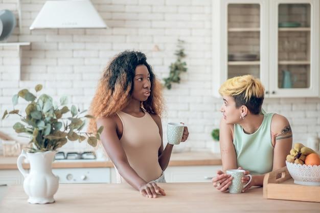Ogólne zainteresowanie. dwóch młodych dorosłych martwiło się dziewczynami w zwykłych ubraniach, komunikujących się przy piciu kawy w kuchni w domu