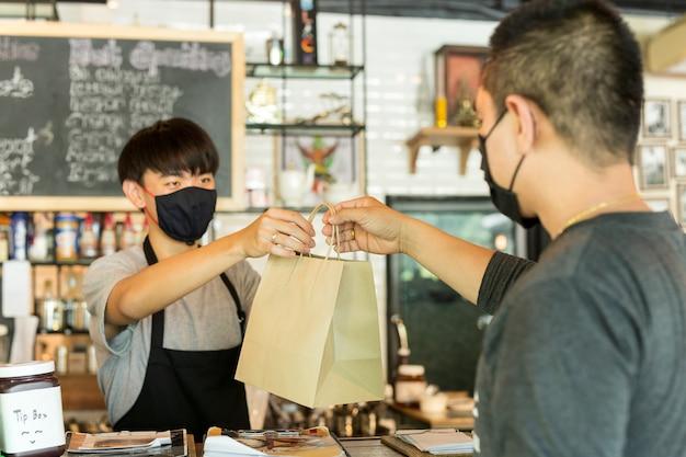 Ogólnospołeczny dystansowy konceptualny kelner daje takeaway torbę klient przy kawiarnią.