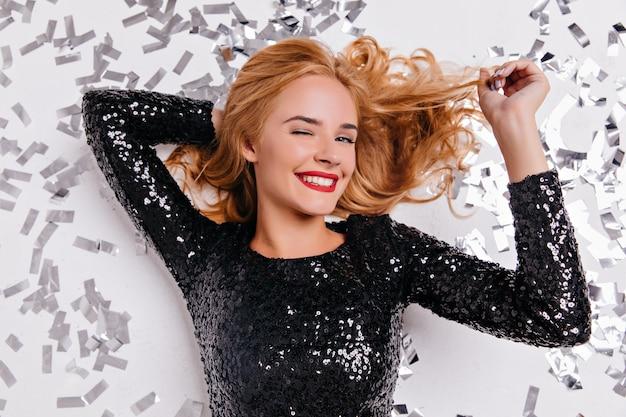 Ogólny portret atrakcyjnej kobiety leżącej na konfetti. błoga jasnowłosa dziewczyna korzystających z przyjęcia urodzinowego.