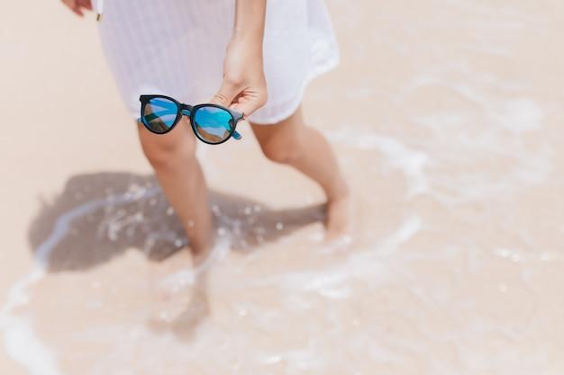 Ogólny portret kobiety stojącej w wodzie na wybrzeżu. plenerowe zdjęcie wyrafinowanej opalonej kobiety z błyszczącymi okularami przeciwsłonecznymi w dłoni.