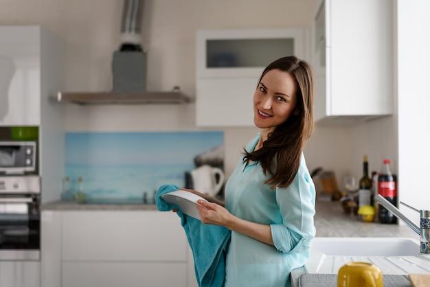 Ogólny portret młodej dziewczyny we wnętrzu jasnej kuchni z ręcznikiem i talerzem w dłoniach. prawdziwe życie