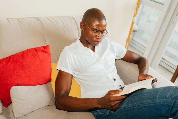 Ogólny widok afrykańskiego człowieka siedzącego na kanapie czytając książkę
