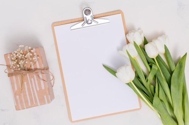 Ogólny widok białych kwiatów tulipanów; pudełko i schowek na białym tle