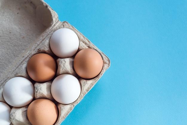 Ogólny widok brązowych i białych jaj kurzych w otwartym kartonie jaj na jasnoniebieskim tle
