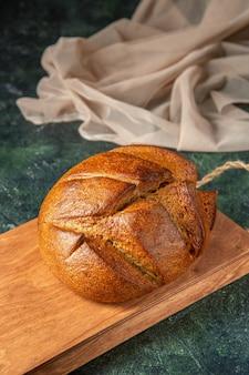 Ogólny widok całego świeżego czarnego chleba na brązowej drewnianej desce do krojenia na powierzchni ciemnych kolorów