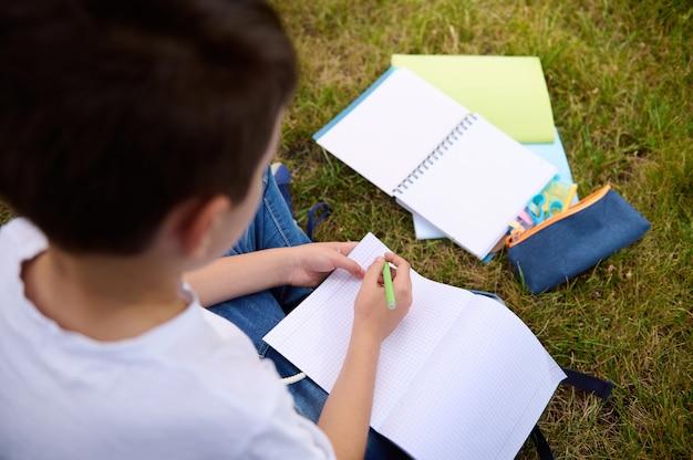 Ogólny widok chłopca w szkole pisania na pustych pustych arkuszach skoroszytu. widok z tyłu elementarnego dziecka w wieku odrabiania zadań domowych w parku po szkole. przybory szkolne leżące na trawie