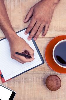 Ogólny widok człowieka pisania na pamiętniku przy stole przez ciasto kawy i filiżanki
