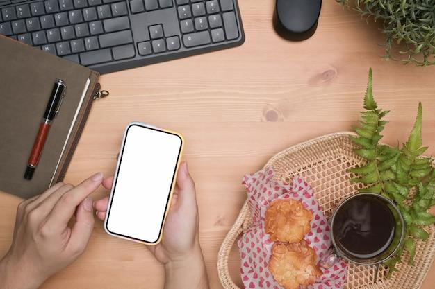 Ogólny widok człowieka przy użyciu telefonu komórkowego na drewnianym stole.