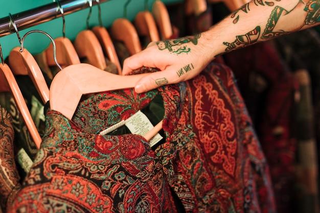 Ogólny widok człowieka z tatuażem w ręku patrząc na ubrania wiszące na szynie