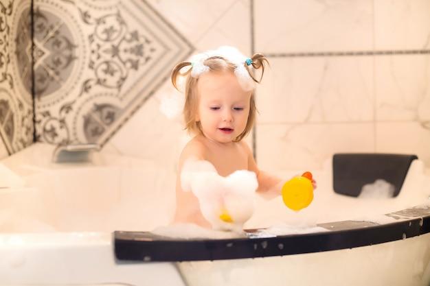 Ogólny widok dziecka bawiące się z rubby kaczek w wannie