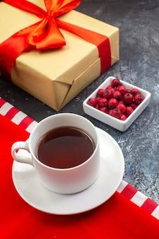 Ogólny widok filiżanki czarnej herbaty na czerwonym ręczniku i herbatnikach na białym talerzu prezent z czerwoną wstążką i dereń na ciemnej powierzchni