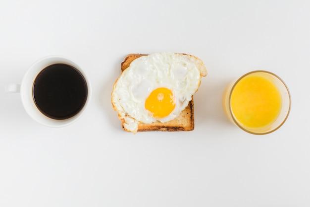 Ogólny widok filiżanki herbaty; szklanka soku i tosty z chleba z jajkiem sadzonym na białym tle