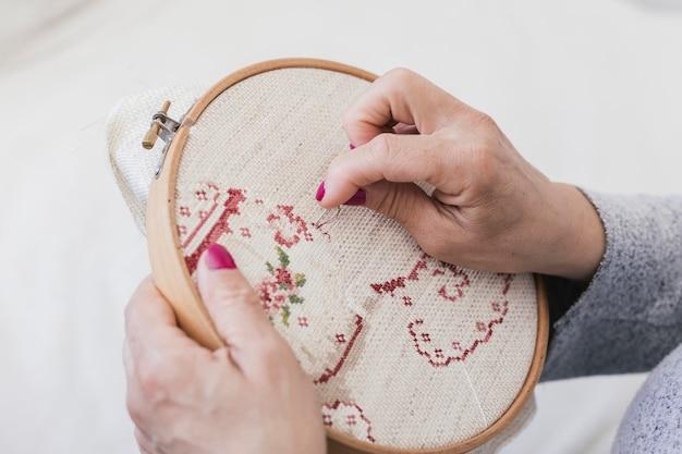 Ogólny widok haftowania kobiety na obręczy z przeszyciami z igłami