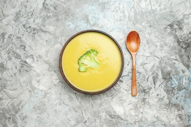 Ogólny widok kremowej zupy brokułowej w brązowej misce i łyżką na szarym stole