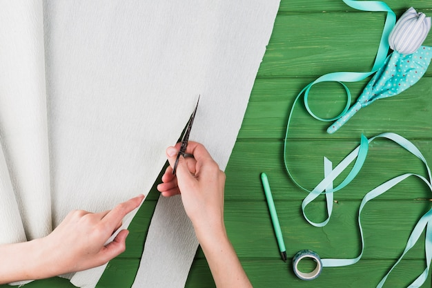 Ogólny widok ludzkiej ręki cięcia krepy papieru w pobliżu pióra; sztuczny kwiat; taśma klejąca i wstążka na zielonym stole