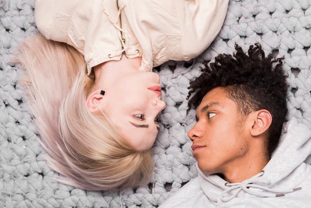 Ogólny widok międzyrasowej młodej pary leżącej na dywanie patrząc na siebie