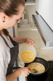 Ogólny widok młodej kobiety przygotowuje spaghetti w kuchni