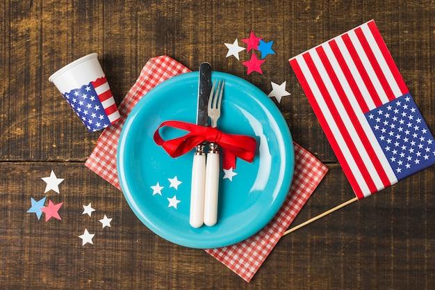 Ogólny widok niebieski talerz i sztućce z flagą usa i szkła jednorazowego użytku na drewnianym stole