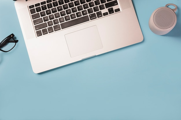 Ogólny widok okularów; głośnik bluetooth i laptop na niebieskim tle