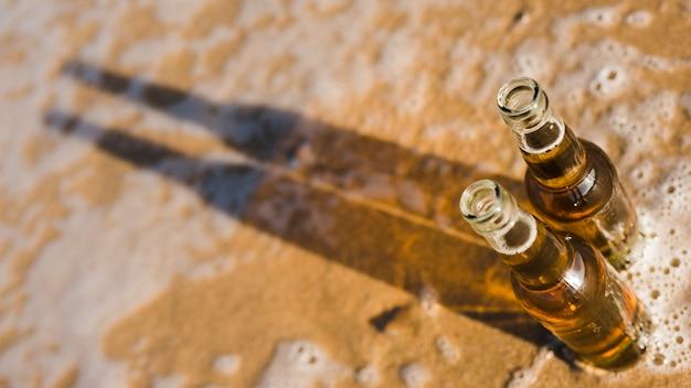 Ogólny widok otwartych butelek piwa z cieniem na płytkiej wodzie na plaży