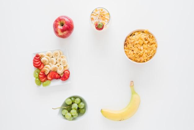 Ogólny widok płatków kukurydzianych z jabłkiem; banan; truskawka i winogrona na białym tle