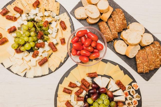 Ogólny widok pomidorów, winogron, wędzonych kiełbasek i półmiska serowego z kromkami chleba