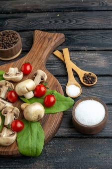 Ogólny widok przypraw surowych grzybów i pomidorów na drewnianym ręczniku na czarnym tle