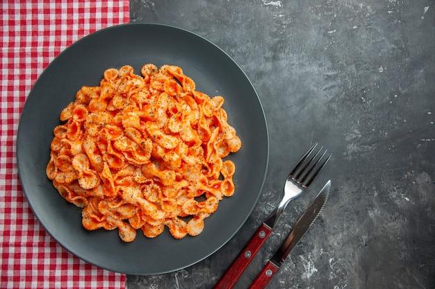 Ogólny widok pysznego makaronu na czarnym talerzu na obiad na czerwonym ręczniku w paski i sztućcach na ciemnym tle