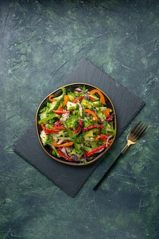 Ogólny widok pysznej sałatki warzywnej z różnymi składnikami na czarnej desce do krojenia na ciemnym tle