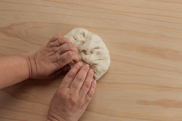 Ogólny widok rąk dorosłej kobiety ugniatającej ciasto do pizzy w drewnianym stole w kuchni