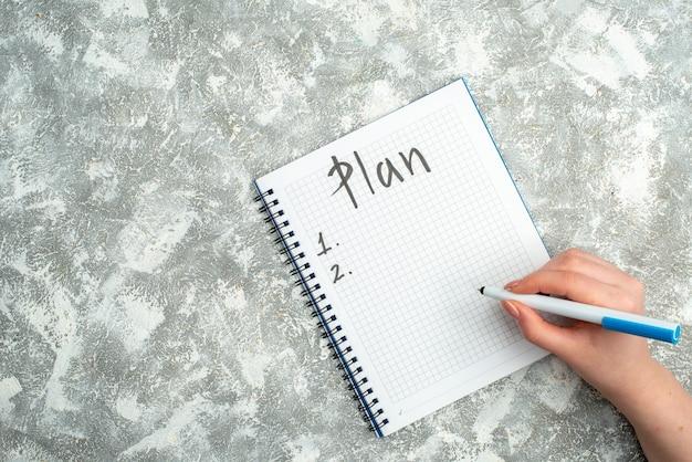 Ogólny widok ręcznego pisania na spiralnym notatniku na szarym tle