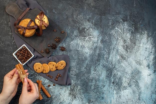 Ogólny widok ręki trzymającej domowe ciasteczka cynamonowe limonki na drewnianej desce do krojenia na ciemnym ręczniku ziarna kawy na lodowym tle