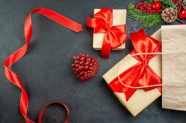 Ogólny widok rolki szyszek iglastych czerwoną wstążką i gałęzi jodły prezent na ciemnym stole