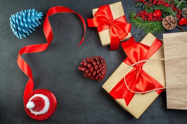 Ogólny widok rolki szyszek iglastych czerwoną wstążką i gałęzi jodły prezent na ciemnym tle