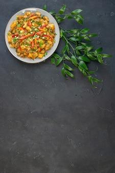 Ogólny widok smacznego posiłku z ziemniakami i warzywami zielonymi liśćmi na czarnym tle z wolną przestrzenią
