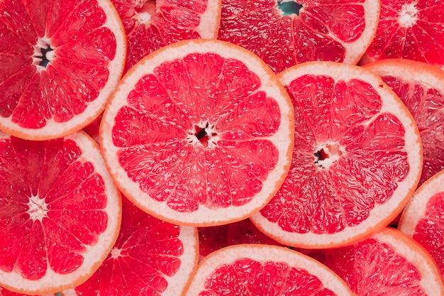 Ogólny widok soczystych czerwonych grejpfrutów tle plasterków