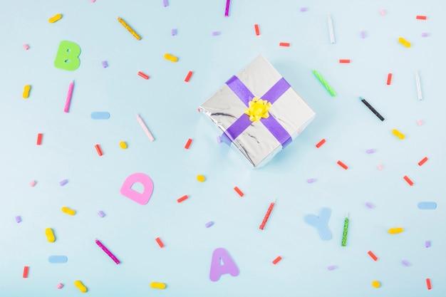 Ogólny widok srebrne pudełko otoczone cukierków i świec na urodziny