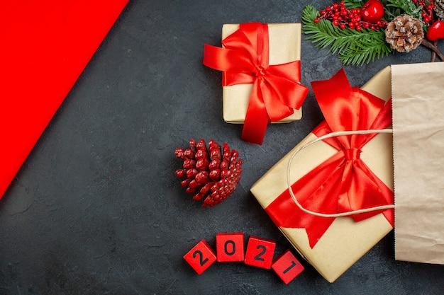 Ogólny widok świątecznego nastroju z szyszkami iglastymi i numerami gałęzi jodły prezent na ciemnym stole