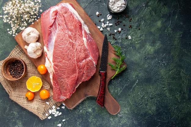 Ogólny widok świeżych surowych czerwonych mięs zielony czosnek na brązowej drewnianej desce do krojenia pomidory pieprz na nagim kolorze nóż do ręczników na ciemnym tle