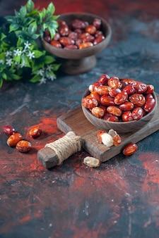 Ogólny widok świeżych surowych owoców srebra jagodowego w drewnianej misce na desce do krojenia i doniczce na tle mix kolorów