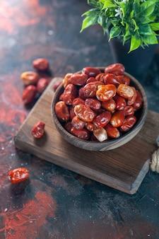 Ogólny widok świeżych surowych owoców srebra jagodowego w misce na drewnianej desce do krojenia i doniczce na tle mix kolorów