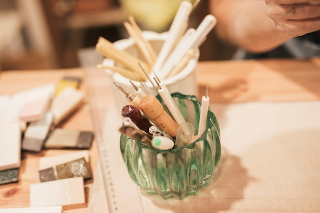 Ogólny widok szklanego uchwytu z różnymi typami narzędzi ręcznych na drewnianym biurku