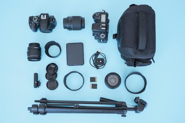 Ogólny widok torby i urządzenia do fotografii na niebieskim tle