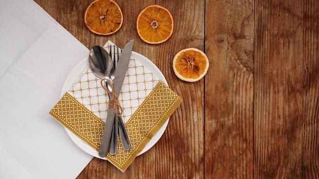 Ogólny widok upadku święto dziękczynienia lub ustawienie stołu bożego narodzenia na drewnianym stole z miejsca na kopię. biały talerz z suszonymi pomarańczami