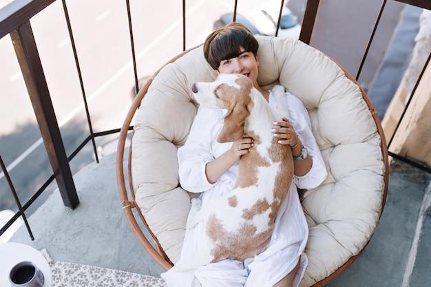 Ogólny widok uśmiechniętej kobiety w białych ubraniach relaksującej w okrągłym miękkim fotelu z psem rasy beagle