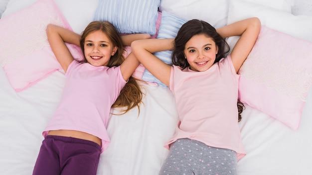 Ogólny widok uśmiechniętych dwóch dziewczyn leżących na łóżku patrząc na kamery