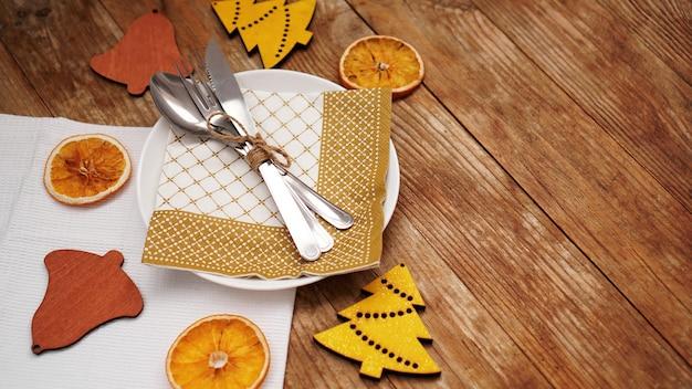 Ogólny widok ustawienia świątecznego stołu na drewnianym stole z miejsca na kopię. biały talerz z suchymi pomarańczami i drewnianymi figurkami świątecznymi